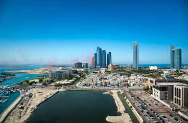 Abu Dhabi skyline with air show colors in the sky and view of the downtown modern buildings