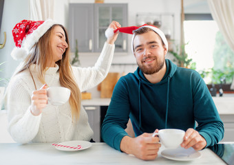 young married couple in Christmas hats drinks coffee in the kitchen