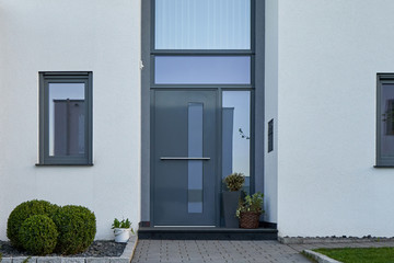 Facade of a modern house with a gray front door and potted flowers. Fotomurales