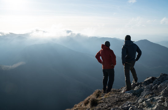 Two men standing standing with trekking poles on cliff edge and looking at sunset rays over the clouds. Successful summit concept image.