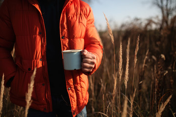 Style man in down jacket with cup of coffee