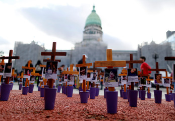 Crosses with pictures of victims of violence are seen in front of the National Congress in Buenos Aires