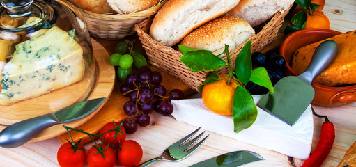 Buffet food -  bread in baskets, wine, fruit, chilli and cheeses - food concept as a panorama / banner / header.