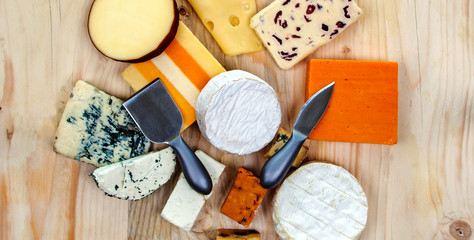 Cheese platter feast - cheese board / selection - cheddar, gloucester, stilton, gorgonzola, red leicester, feta, roule, camembert, brie, smoked, spicy...  panorama / design / banner / header.