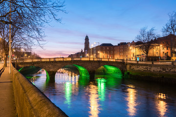 Four Courts and bridge over river Liffey illuminated at night in the city of Dublin in Ireland.