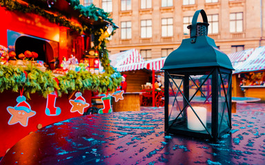 Street lamp with candles at Christmas Market at Riga in Winter Latvia. Light lantern on Advent Fair Decoration and Stalls with Crafts Items on Bazaar. Latvian street Xmas and holiday