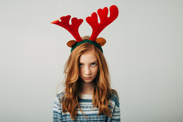 The red-haired girl was offended by her parents on Christmas evening. Blue-eyed cutie at friends with a New Year's gift. Teenage mood is changing. Separately on a white background. Family problems