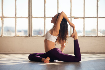 Young athletic woman doing King Pigeon yoga pose in urban space by large window