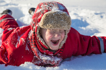 Adorable laughing boy at the snow background
