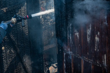 Strong brave firefighter using extinguisher and water from hose for fire fighting. Firefighter...