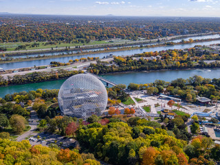Aerial view of Montreal, Quebec, Canada showing architectural landmark Biosphere Environment Museum and maple trees changing color in fall season.