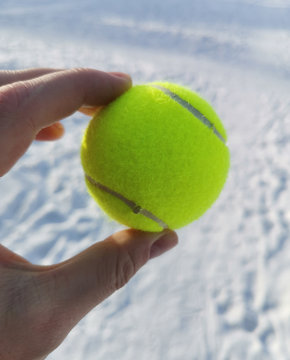 green ball in hand on snow background