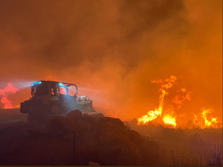 A bulldozer works at the scene of the Cave fire in Los Padres National Forest near East Camino Cielo
