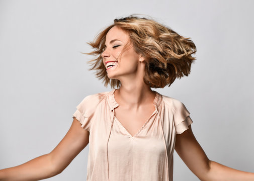 young woman in a beige short-sleeved satin blouse shakes her head with her hair. The concept of joy, happiness, joy, fun.