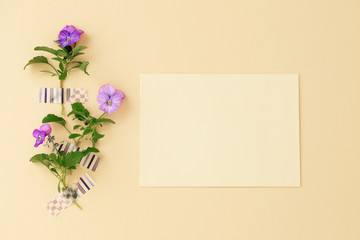 Wall Mural - Beautiful purple viola flowers and blank yellow card.Flat lay, top view, copy space.