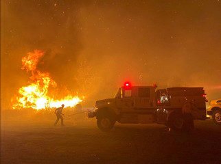 Firefighters battle flames along a highway during the Cave fire in Los Padres National Forest