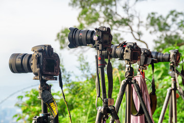 Unusual view of row of professional cameras on tripods