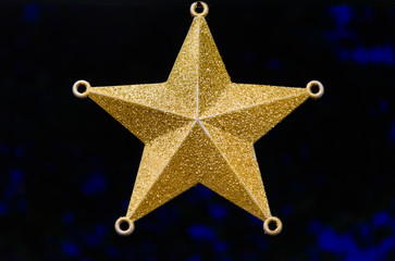 A single Christmas golden star ornament is hanging against a dark background