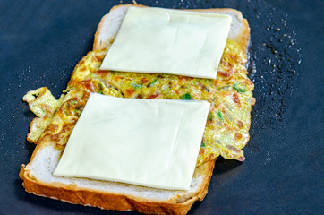 Cheese slices and omelette on Bread slices on a hot pan on the way to become a delicious egg sandwich.