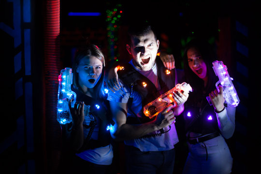 Friends with laser guns in lasertag room