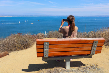Rear view of a Filipino American woman taking a photo from the Cabrillo National Monument Bayside Trail.