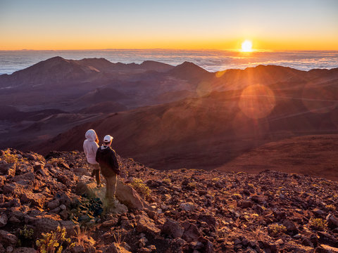 Man and woman couple checking out the sunrise at Haleakala  National Park in Maui, Hawaii.