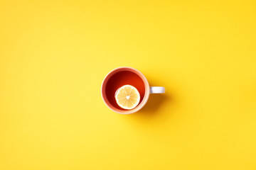Cup of tea with lemon on yellow background. Top view. Copy space. Banner. Autumn or winter season concept
