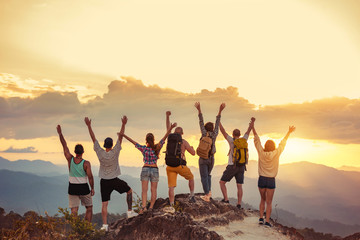 Happy friends stands with raised arms against sunet mountains Fotomurales