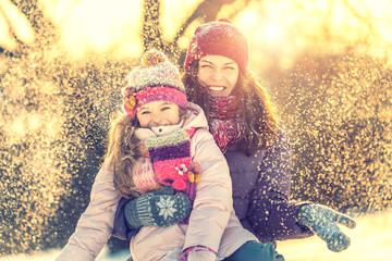 Little girl and her mother playing outdoors at sunny winter day. Active winter holydays concept.