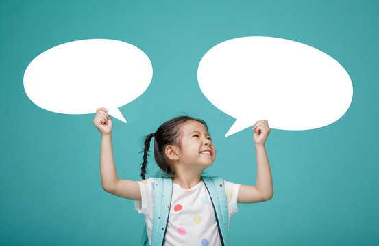 Smiling happy Asian little girl with blank speech bubbles, empty space in studio shot isolated on colorful blue background, Educational concept for school