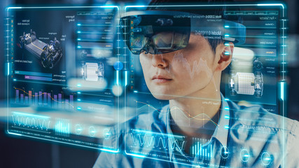 Industrial Factory Chief Engineer Wearing AR Headset Designs a Prototype of an Electric Car Chassis on the Holographic Projection Blueprint. Futuristic Virtual Design of Mixed Technology Application.