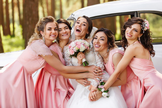 Wedding photography of happy bride and bridesmaids in pink dresses embracing with smile on wedding day