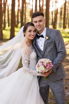 Wedding portrait of stylish newlyweds. Happy couple, bride and groom are smiling and looking at the camera. Classic wedding photo in a frame