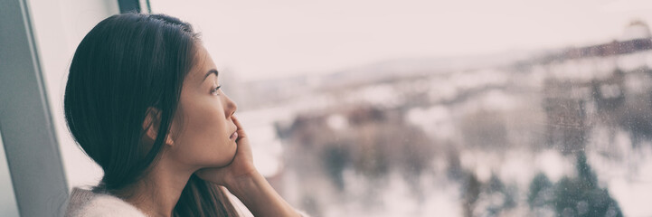 Depressed with seasonal affective disorder Asian woman looking out the window at winter outside banner panorama. Depression, melancholy, sadness people.