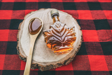 Maple syrup bottle Quebec cultural food traditional harvest top view on buffalo dining tablecloth...