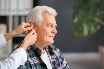 Doctor putting hearing aid in mature man's ear in clinic