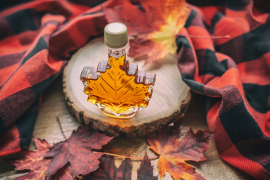 Maple syrup gift bottle in red maple tree leaves for tourist souvenir. Canada grade A amber sweet natural liquid from Quebec sugar shack maple trees farm.