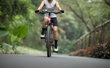 Woman cyclist riding mountain bike on tropical forest trail