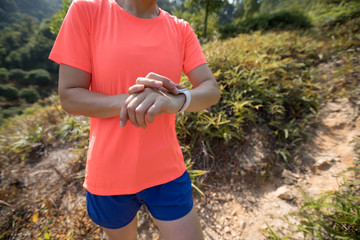 Woman trail runner set her smartwatch before running at tropical forest mountain trail