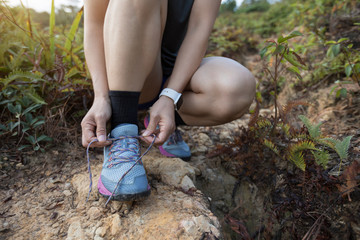 Woman trail runner tying shoelace on forest trail