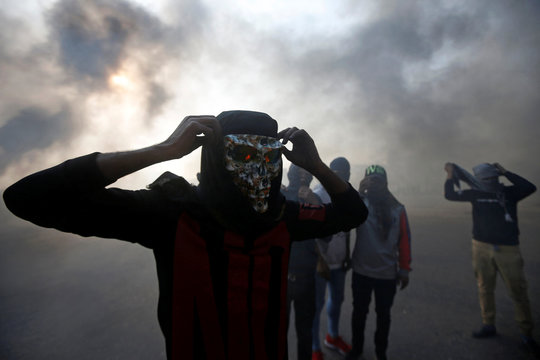 A protester wears a mask amid a cloud of smoke from burning tires during ongoing anti-government protests in Basra