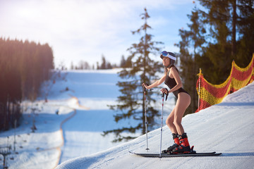 Poster Glisse hiver Sexy attractive young woman in black swimsuit, helmet and goggles standing on skis on steep hill track on background of mountain landscape on sunny winter day. Extreme sports and recreation concept.