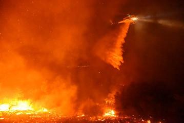A helicopter battles flames off Highway 154 north of Santa Barbara, California