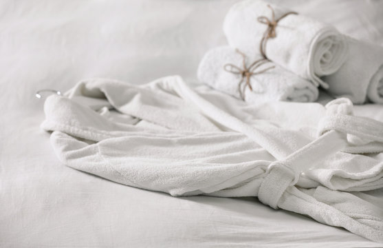 Clean soft bathrobe and towels on bed