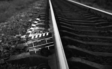 Black clapperboard with train tracks on background. Directing and filming cinema movie. Travel story. Black and white photo.