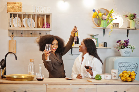 Two african american female friends women spending time at kitchen with wine. Black girlfriends  relaxing at home.