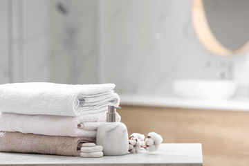 Clean towels, spa stones and soap dispenser on table in bathroom. Space for text