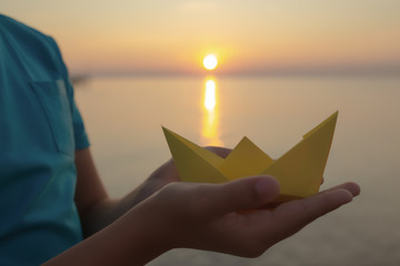Closeup view of hands of young kid holding paper yellow ship in hands isolated at sunny golden sunrise or sunset landscape. Horizontal color photography.