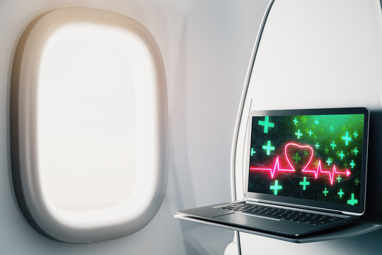 Laptop closeup inside airplane with heart health pic on screen. Medical education concept. 3d rendering.