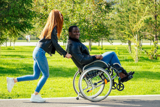 afro american man sitting on wheelchair ,his redhaired ginger girlfriend rolling stroller in autumn park. having romantic date